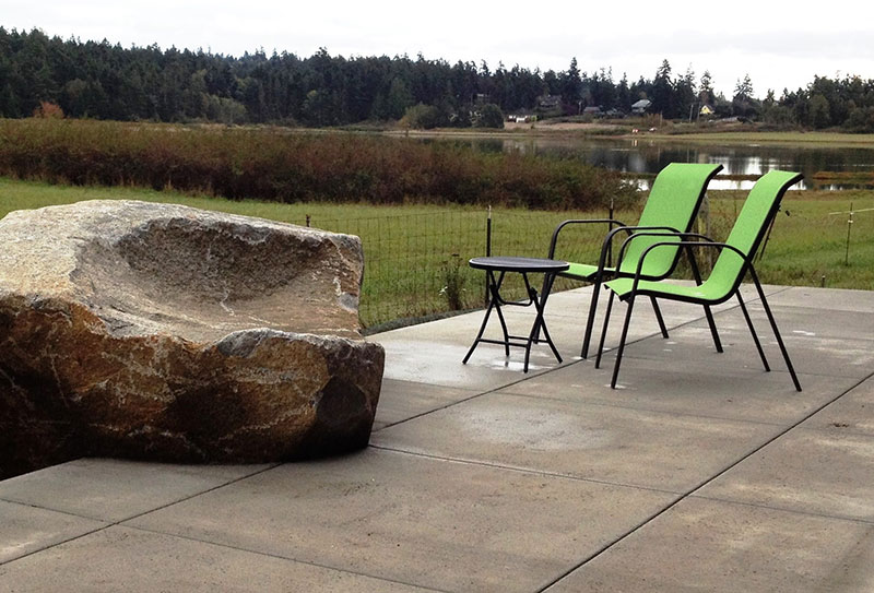 A large sitting rock softens look of otherwise minimalist patio of unstained poured concrete with a brushed finish.