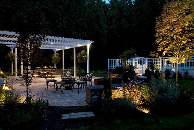 Downlights in arbor illuminate patio area while uplights showcase tree to right. Photo courtesy of Nyce Gardens. & Outdoor Lighting to Brighten Your Seattle Landscape