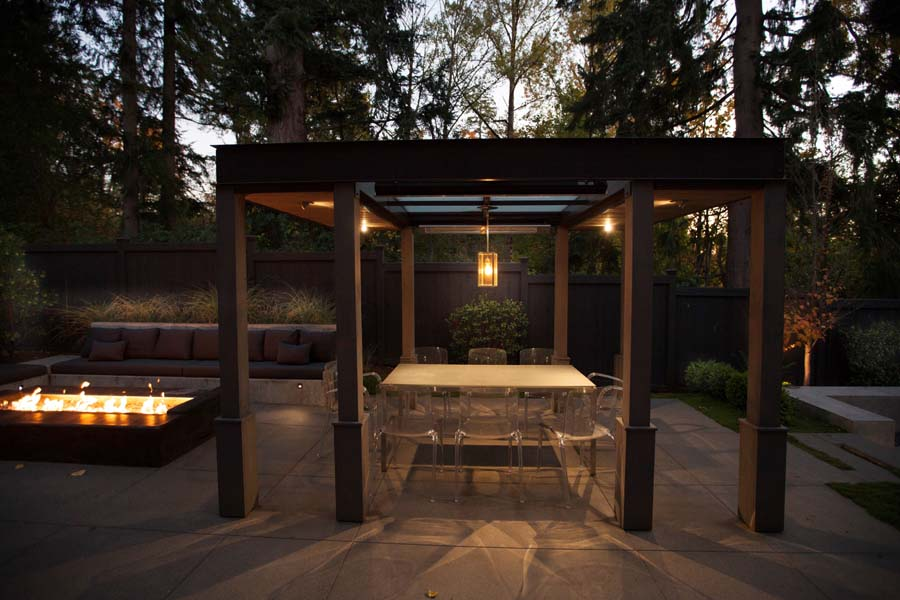 Modern outdoor dining and firepit area designed by landscape architect Kim     Rooney lends itself to intimacy while also offering opportunities for     distancing. The wood arbor framing the dining area has heaters and glass     panels in the ceiling.