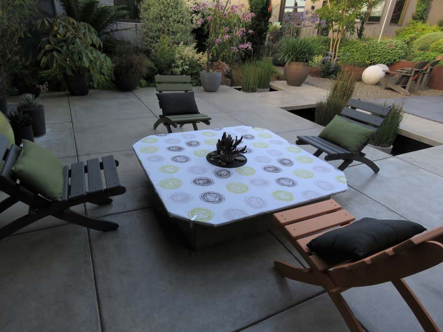 Here, a 5- by 5-foot tabletop was fitted over a built-in firepit so that a     small group could socialize safely. As evening temperatures drop, the     tabletop is lifted off so conversation can continue beside a warm fire.