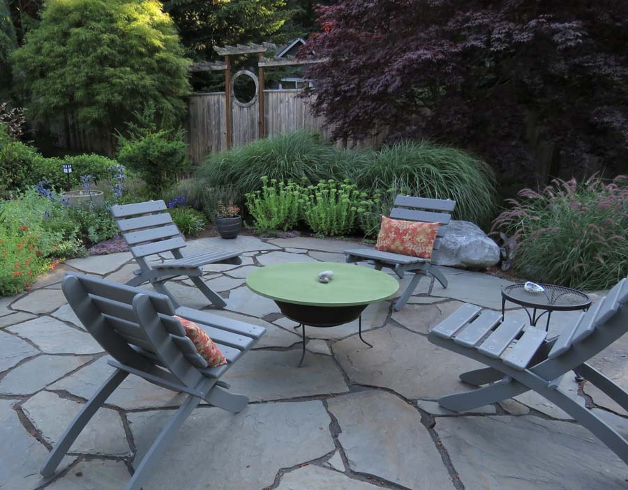 This versatile backyard patio has distanced seating, a firepit that doubles     as a coffee table, and a bubbler fountain that attracts birds but only     required leveling and an outlet to operate.