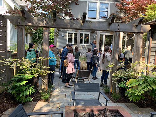 People on patio with plantings and wooden trellis listening to speaker.