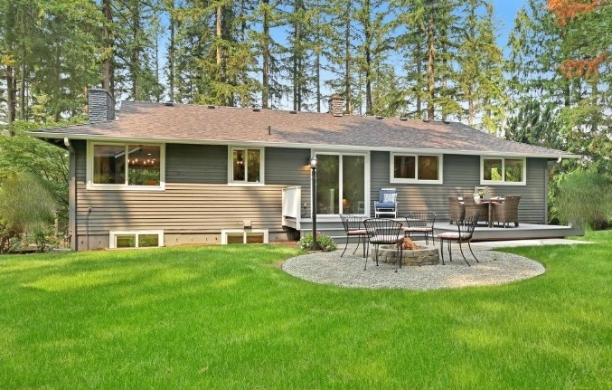 Back of home and backyard with lawn and deck with chairs and table with circular patio are with chairs and firepit.