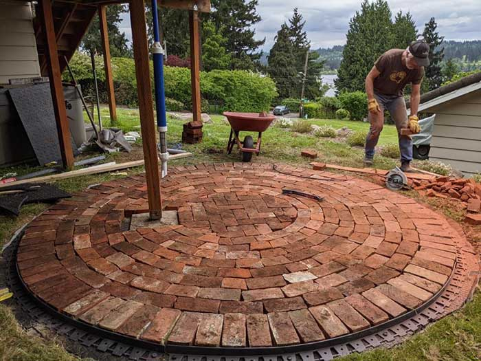 Man placing terra cotta colored pavers in a circular pattern for a patio