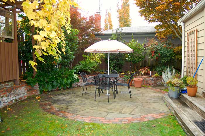 Circular flagstone patio with brick edging with black table and chairs.     raised brick garden bed surrounds patios and is filled with green plants