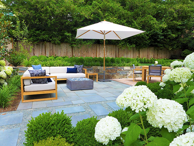 Patio with umbrella and outdoor sofas, firepit and table and chairs on slate and gravel with surrounding plantings.
