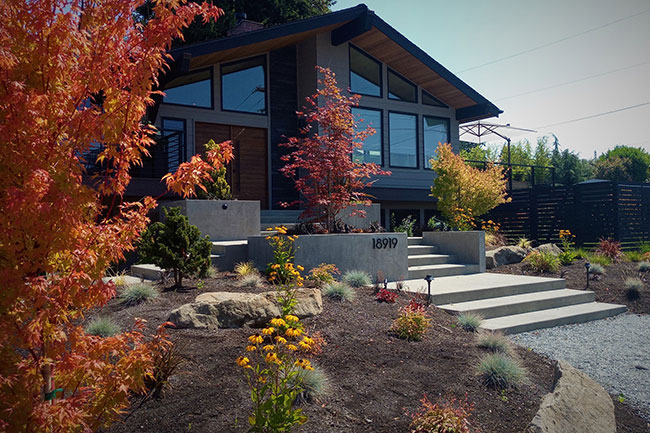 Front of home with fall color in trees, steps and gravel walk way