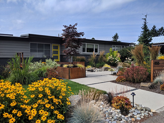 Front of home showing flowers, walk way, planter boxes, garden lights and lawn