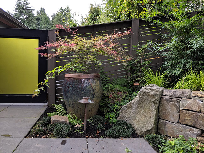 Side yard of same home with rock wall, large concrete pavers, large container with plant, fence and gate
