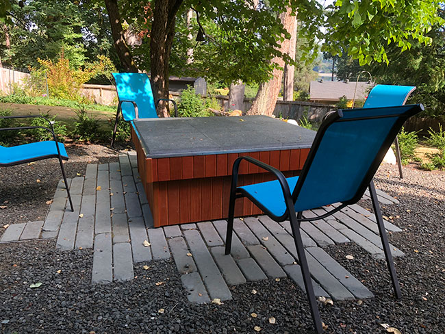 custom garden table with seats and paving