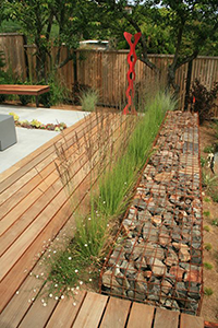 The two tiered rear yard space was separated using a custom gabion wall. Plantings and decking direct the viewer to the 'DNA' sculpture at the end of the deck.