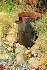 A steel container water feature while industrial in nature, softens the space with a constant noise of splash and movement. This is a pond-less feature minimizing maintenance.