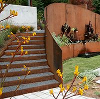 The spiral stair brings the visitor to the inner garden space, where the custom spa and spilling water feature brings inward focus to the space. The steel wall was acid washed to accelerate the corrosion process. The cannas and artemesia, chosen for their heat tolerance, were planted just one month prior to this shot. Anigozanthos in the foreground container.