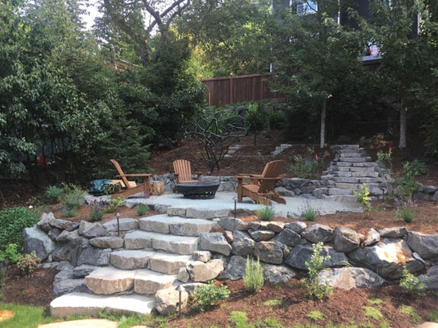 West Seattle gravel firepit patio, ¼-minus compacted firm. Second set of stone stairs lead to a hammock grotto with posts for 3 hammocks. Notice the metal sculpture just above the gravel patio, it provides one end of support for the hammocks.
