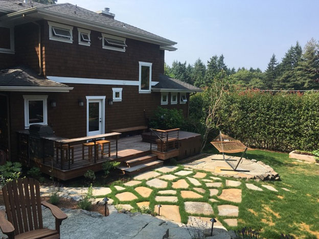 The same project, this view from the gravel patio looking down at the Ipe deck – with built-in gas BBQ and counter top, and sunken hot top – flagstone set in lawn and a flagstone patio.